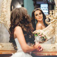 Bride in white wedding dress and mirror